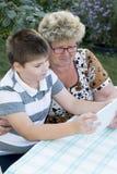 Mamie avec le comprimé de observation de petit-fils en nature Photos libres de droits