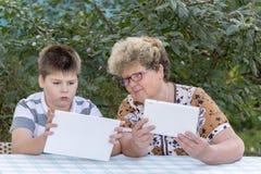 Mamie avec le comprimé de observation de petit-fils en nature Photos stock