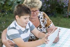 Mamie avec le comprimé de observation de petit-fils en nature Image libre de droits
