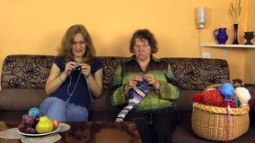 mamie et la petite-fille tricotent ensemble, le sac plein t banque de vidéos