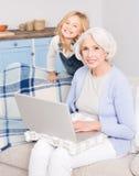 Mamie et petite fille à l'aide de l'ordinateur portable Photo libre de droits