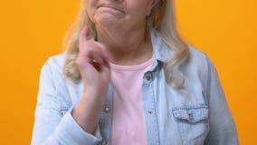 Mamie stricte grondant sur le fond lumineux, faisant des gestes par le doigt, panneau d'avertissement banque de vidéos