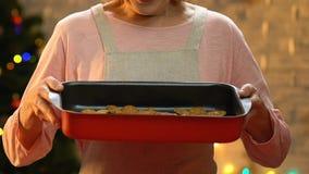 Mamie tient le plateau de cuisson avec les biscuits de gingembre, festins de Noël pour la famille entière banque de vidéos