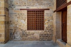 Mamluk era wooden closed window with wooden ornate grid over stone bricks wall, Medieval Cairo, Egypt stock photos