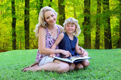 Mamma adorabile e figlia che leggono all'aperto Fotografia Stock Libera da Diritti
