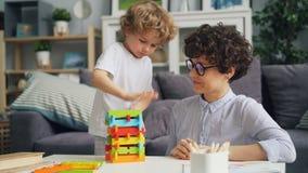 Mamma allegra della ragazza che gioca con il suo piccolo figlio con i blocchi e la risata di legno video d archivio