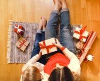 Mamma allegra e sua la ragazza sveglia della figlia che scambiano il GIF di Natale Immagini Stock