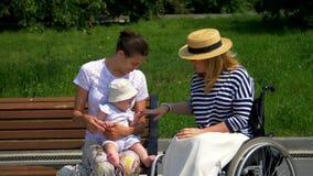 Mamma, barn och flicka i en rullstol stock video