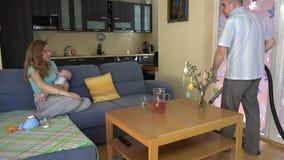 Mamma boos met de mens die vloer schoonmaakt en slaapbaby stoort 4K stock videobeelden