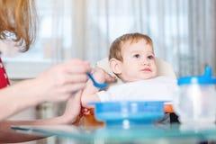 Mamma che alimenta la mano della tenuta del bambino con un cucchiaio di porridge nella cucina Emozioni di un bambino mentre mangi immagini stock