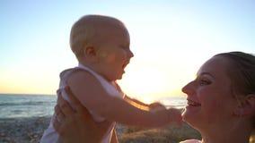 Mamma che coddling con un fare da baby-sitter sulla spiaggia al tramonto video d archivio