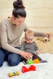 Mamma che dà i giocattoli di plastica al suo bambino gridante fotografie stock libere da diritti