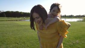 Mamma che dà sulle spalle giro alla figlia speciale stock footage