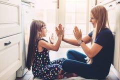 Mamma che gioca con la figlia sul flloor della cucina Fotografie Stock Libere da Diritti