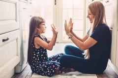 Mamma che gioca con la figlia sul flloor della cucina Immagine Stock
