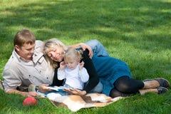 Mamma che legge alla sua famiglia all'esterno Fotografie Stock