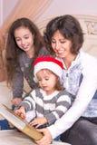 Mamma che legge una storia di Natale con i bambini Immagine Stock