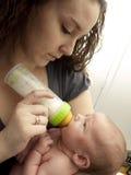 Mamma che nutrito artificialmente bambino Immagini Stock
