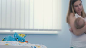 Mamma che oscilla il suo piccolo figlio in armi sul fondo delle sfuocature archivi video