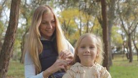 Mamma che pettina capelli di piccola figlia sveglia sulla natura stock footage