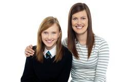 Mamma che propone con le braccia intorno alla sua figlia sveglia Immagini Stock