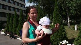 Mamma che tiene il bambino e le passeggiate nel parco video d archivio