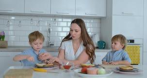 Mamma con due bambini nella cucina alla tavola che prepara hamburger per il pranzo stock footage