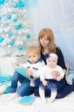 Mamma con i bambini all'albero del nuovo anno immagini stock