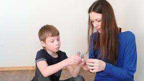 Mamma con i modelli della molecola della costruzione del figlio dell'insieme di plastica colorato della costruzione stock footage