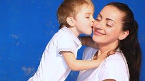 Mamma con il bacio stringente a sé del gioco del ragazzino nella sala video d archivio