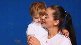 Mamma con il bacio stringente a sé del gioco del ragazzino nella sala archivi video