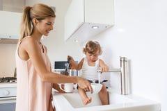 Mamma con il bambino nella cucina Immagine Stock