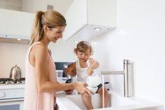 Mamma con il bambino nella cucina Immagini Stock Libere da Diritti
