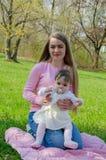 Mamma con il bambino in vestiti luminosi su un plaid rosa sulla destra verde Famiglia che riposa nel parco un giorno caldo fotografia stock libera da diritti