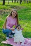 Mamma con il bambino in vestiti luminosi su un plaid rosa sulla destra verde Famiglia che riposa nel parco un giorno caldo fotografie stock libere da diritti