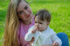 Mamma con il bambino in vestiti luminosi su un plaid rosa sulla destra verde Famiglia che riposa nel parco un giorno caldo fotografia stock