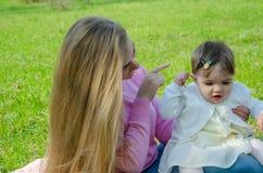 Mamma con il bambino in vestiti luminosi su un plaid rosa sulla destra verde Famiglia che riposa nel parco un giorno caldo fotografie stock