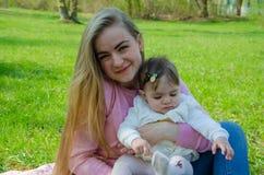 Mamma con il bambino in vestiti luminosi su un plaid rosa sulla destra verde Famiglia che riposa nel parco un giorno caldo immagine stock libera da diritti
