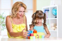 Mamma con il suo gioco da bambini della figlia insieme Immagini Stock Libere da Diritti