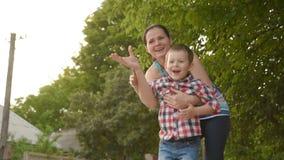 Mamma con l'aeroplano di carta del lancio del bambino archivi video