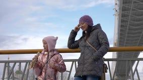 Mamma con la piccola figlia che sta sul ponte e sulla ragazza che mangiano hot dog video d archivio