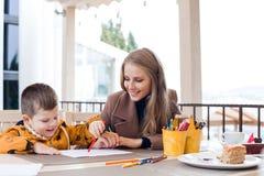 Mamma con le matite colorate tiraggio del ragazzo immagini stock libere da diritti