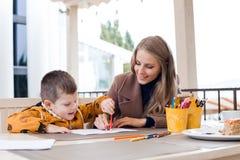 Mamma con le matite colorate tiraggio del ragazzo immagine stock libera da diritti