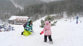 Mamma con le palle di neve di tre anni di un gioco della figlia stock footage