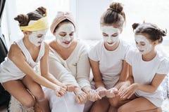 Mamma con le sue figlie che fanno la maschera di protezione dell'argilla fotografie stock