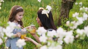 Mamma con un piccolo giardino del succo d'arancia della bevanda della figlia in primavera video d archivio