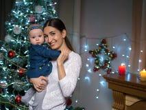 Mamma con una piccola figlia all'albero di Natale fotografia stock