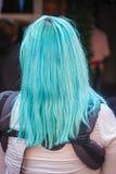 Mamma dai capelli blu con l'imbracatura del bambino che sta con di nuovo alla macchina fotografica fotografie stock