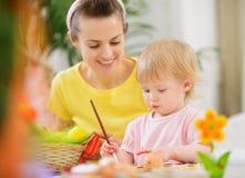Mamma dat baby het schilderen op Paaseieren bevordert Stock Fotografie