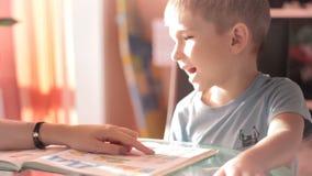 Mamma dat zijn zoon helpt om zijn thuiswerk 3 te doen stock videobeelden